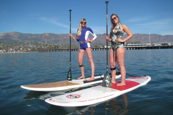 2 girls taking standup paddleboard lessons