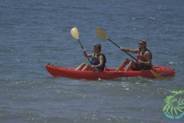 2-kayakers-landing-a-kayak-on-the-beach