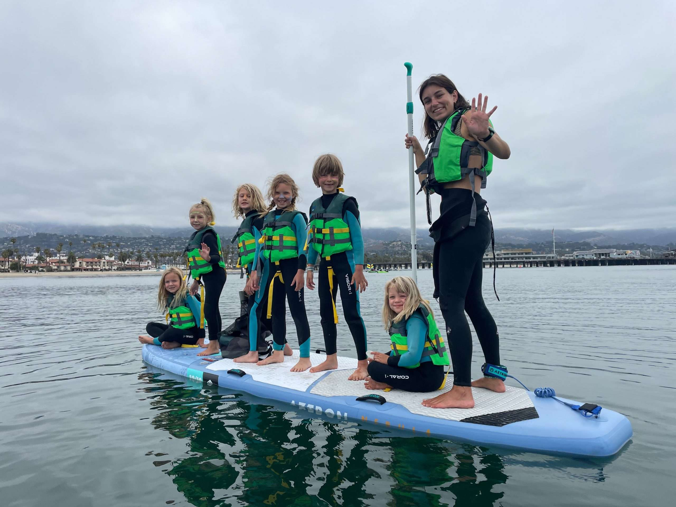 7 kids out on a standup paddle board from Santa Barbara Paddle Sports